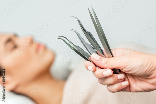 Fotografía Cosmetologist holds tweezers for eyelash extensions on background of patient, close up