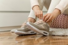 Girl Putting On Sport Sneakers Isolated