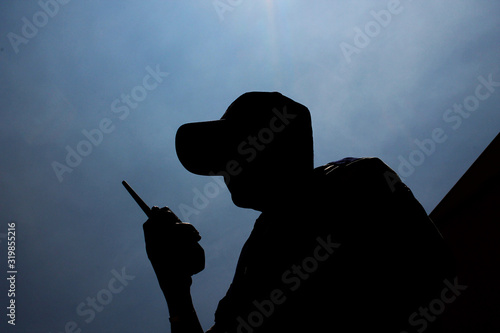 Fotografia, Obraz Low Angle View Of Security Guard With Walkie-Talkie Against Sky