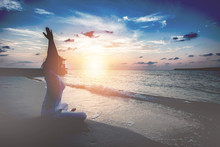 Woman Meditating While Sitting At Beach During Sunset