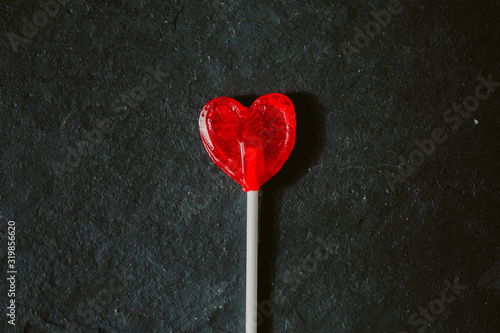 Photographie Close up view of red heart shaped lollipop on black slate background