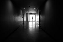 Distant View Of Woman Standing In Corridor
