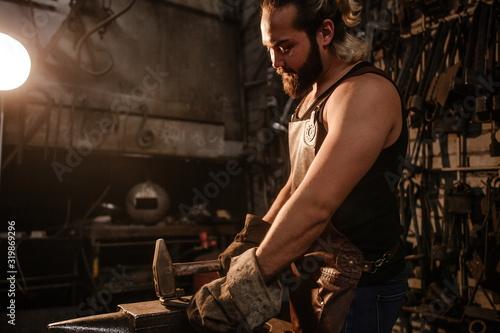 Portrait of a brutal muscular blacksmith standing in a dark workshop forging iro Canvas Print