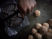 Cropped Hand Preparing Food With Tortilla Press On Table