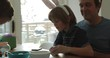 Father and son in costume rabbit ears dyeing Easter eggs