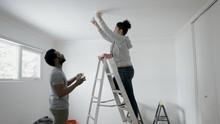 Couple Replacing Light Bulb Wi...