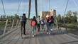 Carefree young adult friends walking and biking along sunny urban footbridge