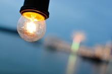 Close-Up Of Illuminated Light Bulb Against Sea