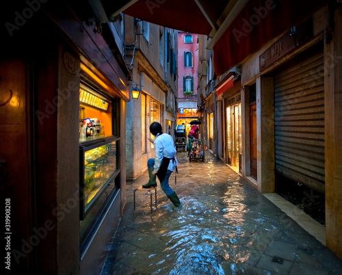 Canvas Print Rear View Of Sales Clerk Climbing On Stool At Water Filled Alley During Flood