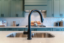 Double Bowl Kitchen Island Sink With Black Faucet Against Cooktop And Cabinets