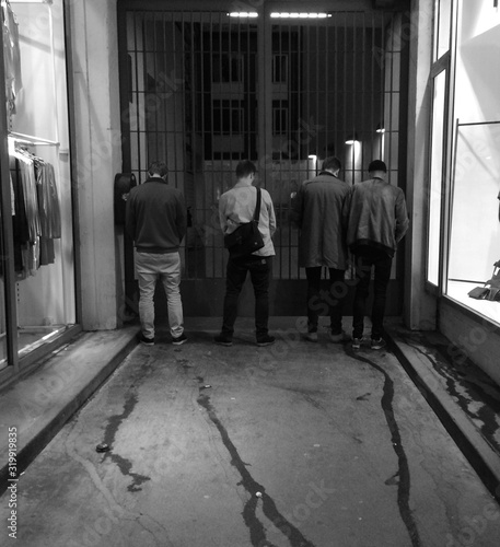 Fotografía Rear View Of Men Urinating On Gate By Store