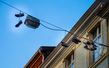 LOW ANGLE VIEW OF Shoes Hung From Telephone Wire AGAINST BLUE SKY