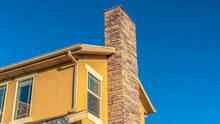 Panorama Frame Home Exterior With Stone Brick Chimney Against Gable Roof And Yellow Wall