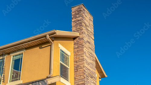 Fotografia Panorama frame Home exterior with stone brick chimney against gable roof and yel