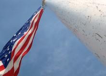 Directly Below Shot Of American Flag Waving Against Sky