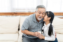 Asian Little Granddaughter Bringing Glass Of Milk To Grandfather. Young Niece Girl Take Care Of Grandpa Kissing Him With Happiness And Smile. Elder Health Care And Senior Family Retirement Lifestyle.