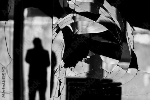 Obraz Reflection Of Silhouette Man On Broken Mirror - fototapety do salonu
