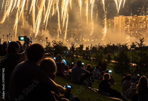 People On Field Looking At Illuminated Fireworks In City During Night