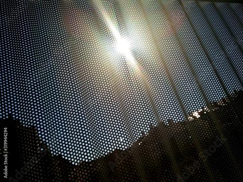 Valokuva Sunlight Falling On Perforated Metal