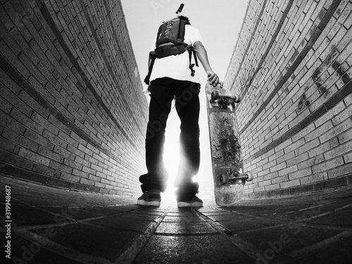 Low Angle View Of Man Holding Skateboard While Standing On Footpath - fototapety na wymiar