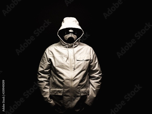 Man With Mask Standing Against Black Background Canvas Print