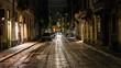 Railroad Tracks On Street Amidst Buildings At Night