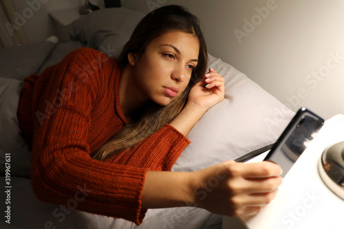 Girl suffering insomnia checks the time on the phone Canvas Print