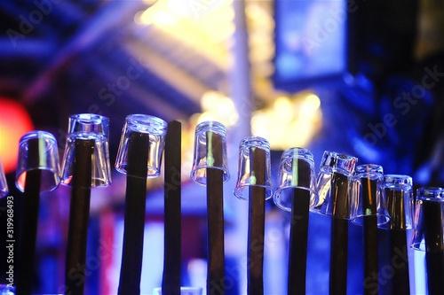 Fotografía Shot Glasses On Bamboos At Illuminated Bar