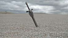 Sword In Sand At Beach Against Cloudy Sky