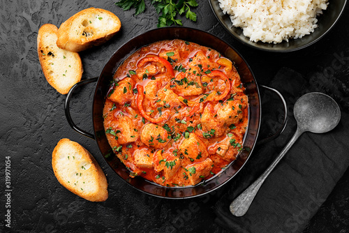 Fototapeta Fish Stew cooked in a delicious  rich and fragrant broth, topped with fresh parsley and served with  rice