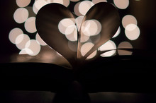 Close-Up Of Heart Shape Made From Book Pages Against Lights