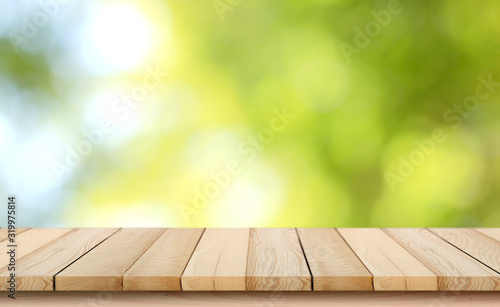 blurred background of green park in summer, Wood table top on shiny bokeh green background Fotobehang