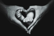 Close-Up Of Mother Hands Making Heart Shape Over Baby Feet Against Black Background