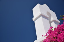 Low Angle View Of Bougainvillea Blooming By Tower Against Clear Blue Sky