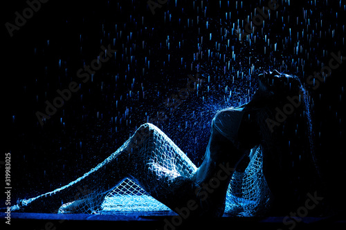 A slender brunette in a swimsuit sits on a black background in the studio under raindrops, illuminated by blue spotlights.