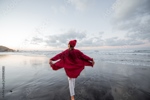 Lifestyle portrait of a carefree woman dressed in red shirt and hat walking on the beach at dusk. Wellness, happiness and life enjoyment concept