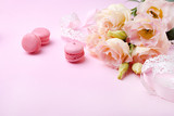 Beautiful pink eustoma flowers and macaron on a pink background