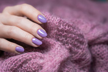 Purple Nail Gel Polish At Fingers Of Woman. Modern Style Of Naildesign.  Female Hand Holding Wool Knitted Material Of Cozy Fluffy Sweater Or Blanket.