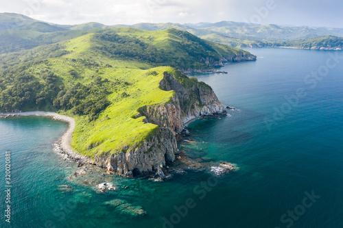 Fototapeta Aerial view of green rocky coastline and clean turquoise sea in Asia.  Cape Azaryev at Gamov Peninsula in summertime. Seaside nature landscape in Primorsky Krai, Far East, Russia obraz