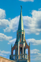 An Old Church Steeple With Bell Tower Against A Blue Sky