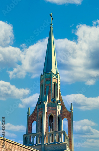 Canvas-taulu An old church steeple with bell tower against a blue sky