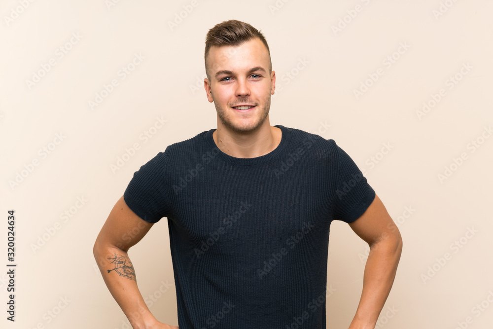 Fototapeta Young handsome blonde man over isolated background posing with arms at hip and smiling