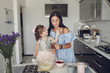 Family in a kitchen. Mother with little daughter. Flour at the table.