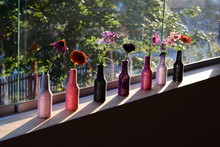 High Angle View Of Various Flowers In Decorated Bottles On Window Sill