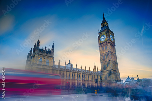 Photo Blurred Motion Of Double-Decker Bus On Street By Big Ben Against Sky During Suns