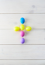 Easter Eggs In The Form Of A Cross On A Light Wooden Background. Vertical Orientation, Top View.
