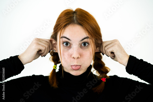 Close up portrait of funny girl holding her ears with hands like a monkey Wallpaper Mural