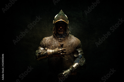 Portrait of a knight in armor holding his sword in his hands Canvas Print