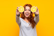 Leinwanddruck Bild - Teenager redhead girl holding an orange over isolated yellow background
