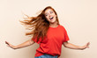 Teenager redhead girl dancing over isolated background